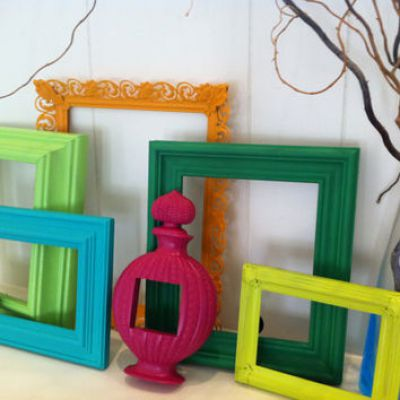 Upcycled picture frames painted different colours and stood up against a white wooden panel wall