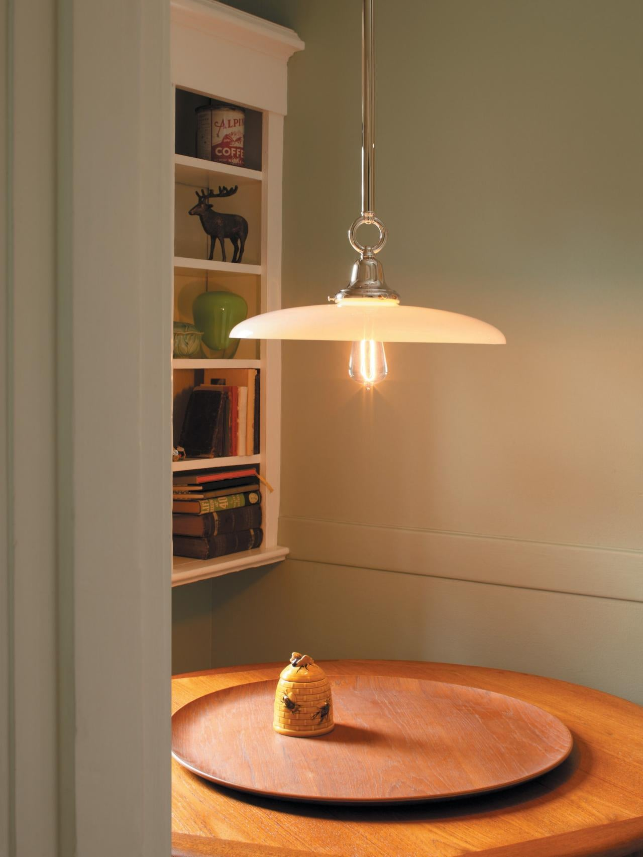 Round white lampshade below head height, suspended over a round wooden table
