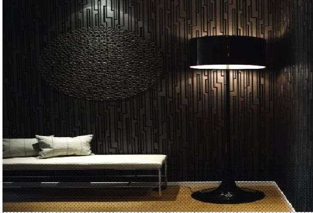 Very dark room with black textured walls and black floor lamp with black round lamp shade