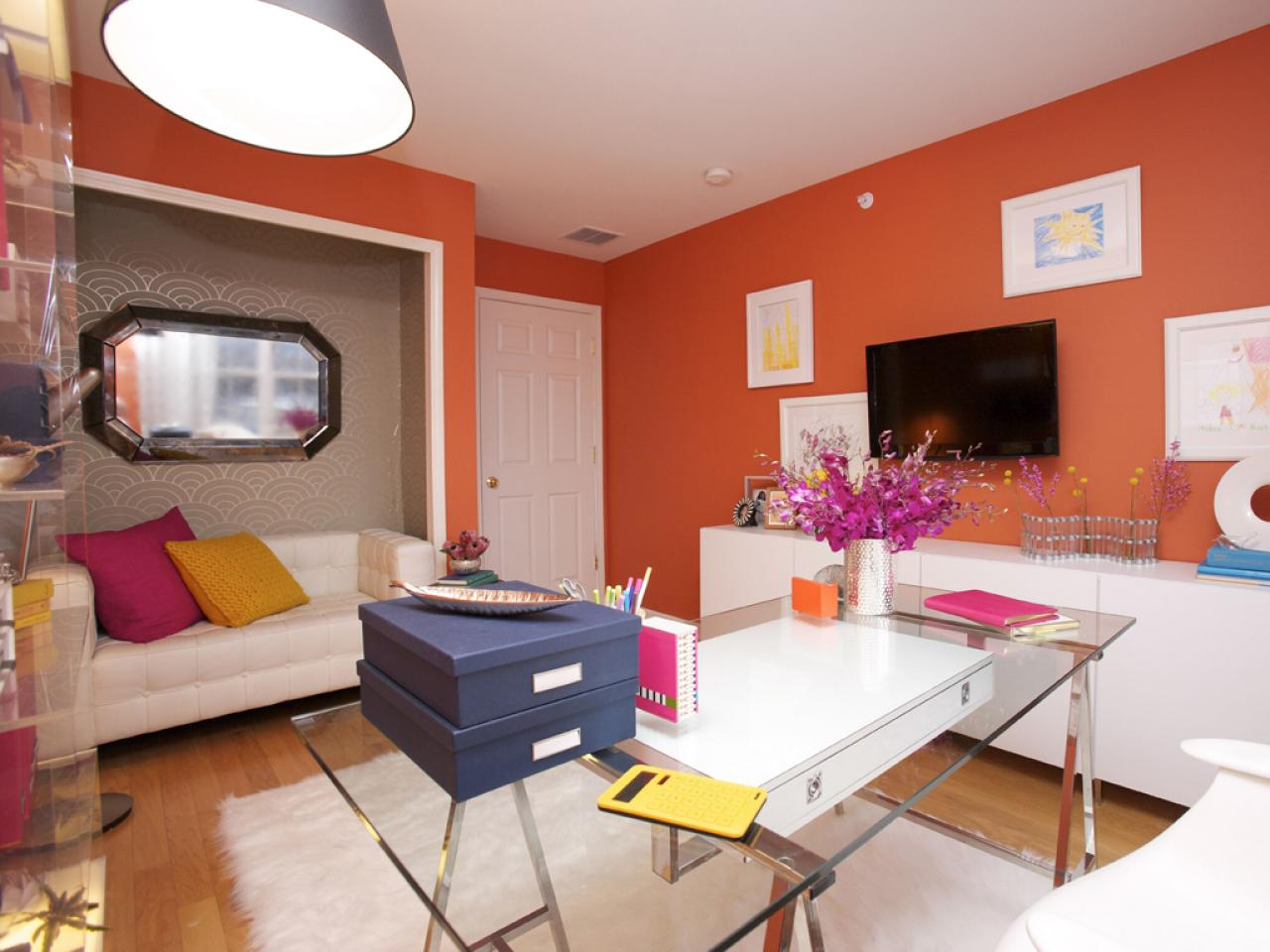 Bright and bold orange office with a cream leather sofa in an alcove