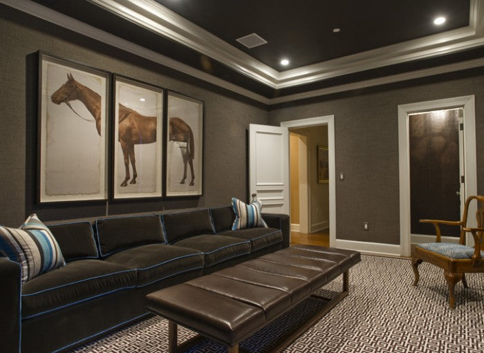 Brown living room with long dark brown chair, dark leather bound coffee table and three cross section photos on the wall of a horse