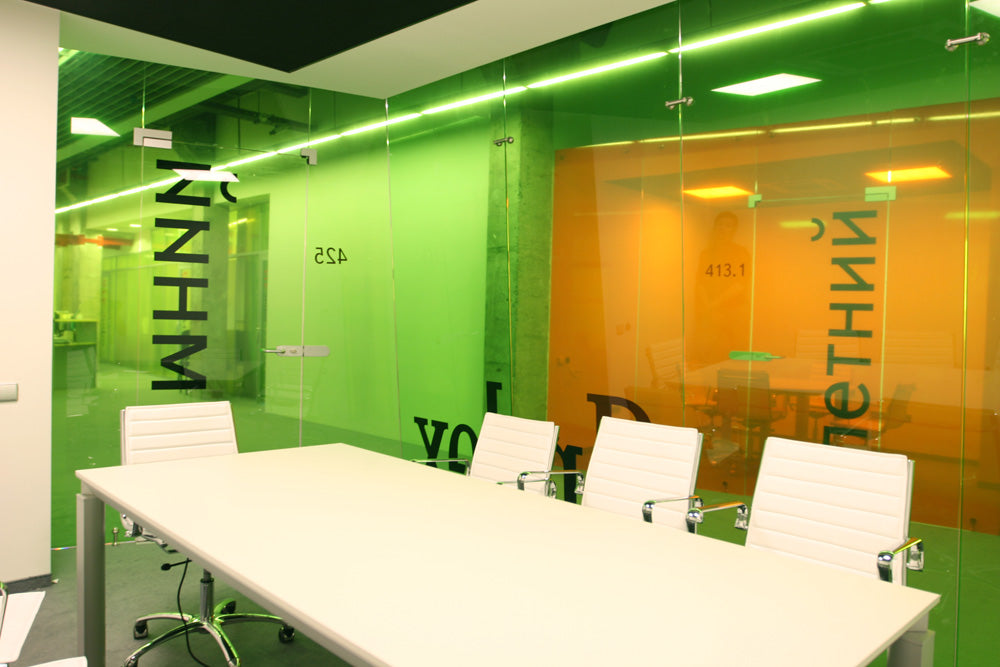 Bright green glass wall office space, with white conference table