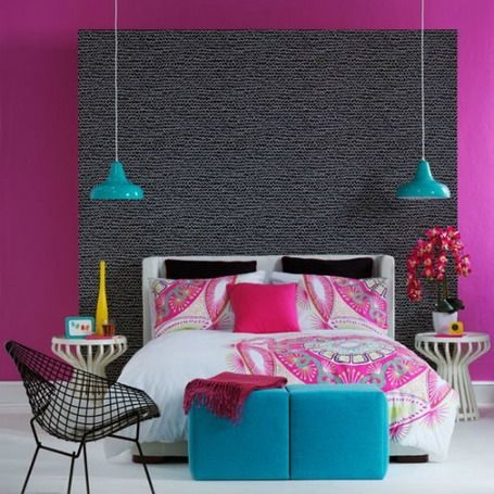 Purple wall colour with grey feature wall art behind the bed, white and pink bedding and teal accessories