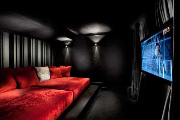 Home cinema with black walls, red day beds and red cushions
