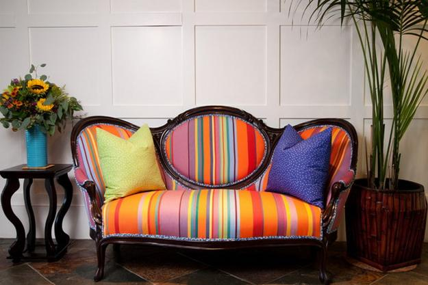 Wooden framed two seater chair upholstered in brightly coloured stripe fabric