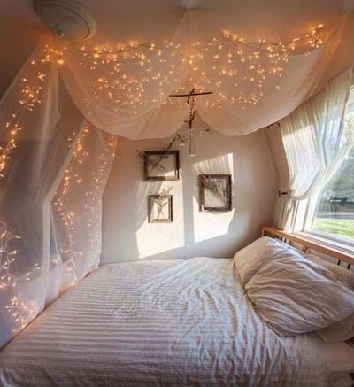 Voile bed canopy and fairy lights over a bed