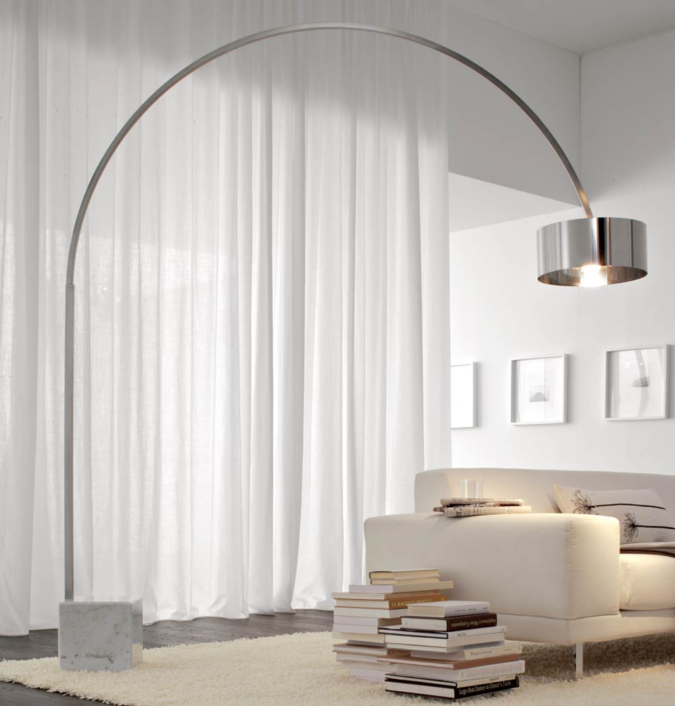 White, light and fresh living room with a large curving metal floor lamp