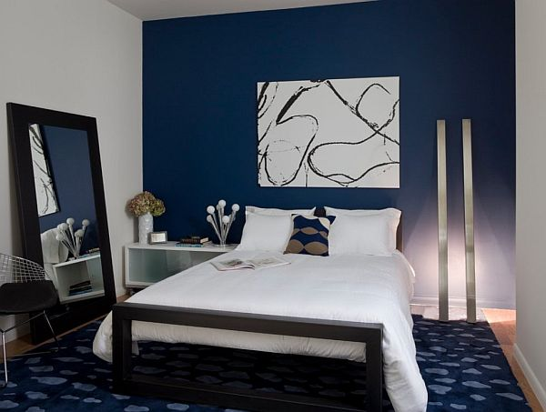 Dark blue and white bedroom, with blue feature wall, rug and white side walls and bedding
