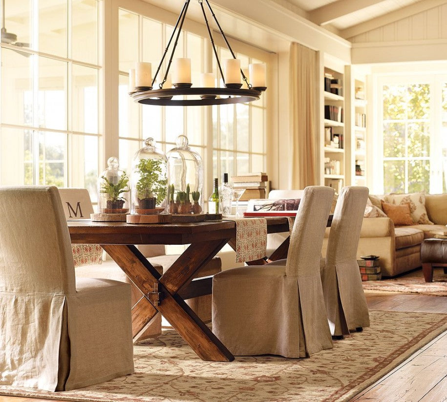Cream and beige dining room with wooden tables and hanging candle chandelier