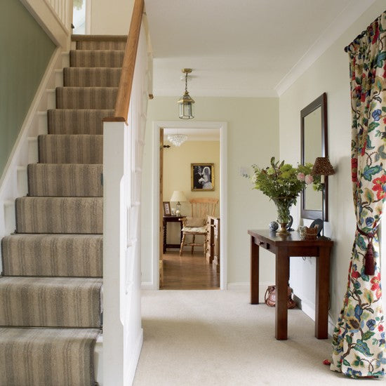 Hallway with cream carpet and white wooden staircase