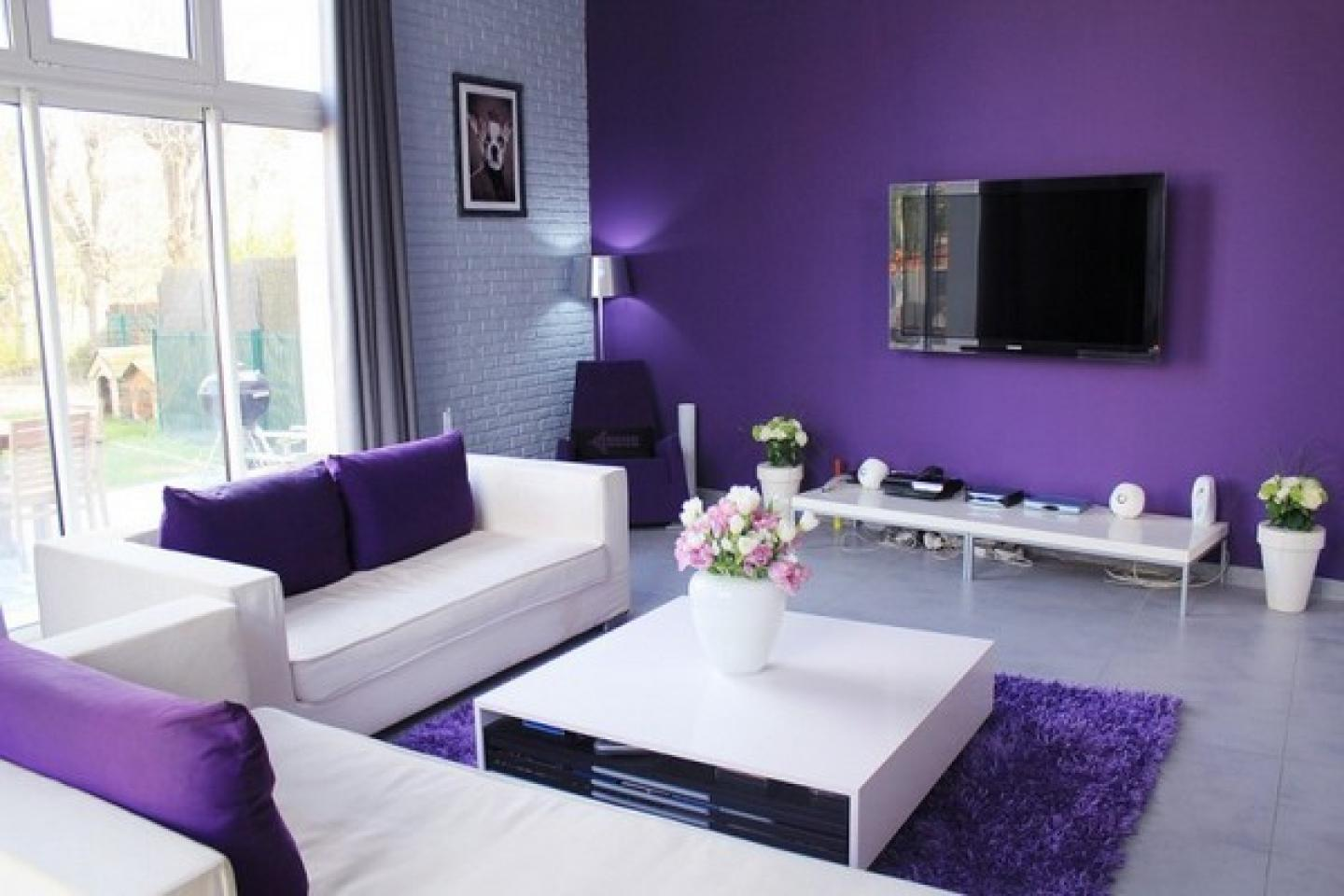 Purple and lilac living room with white sofas facing a wall mounted TV