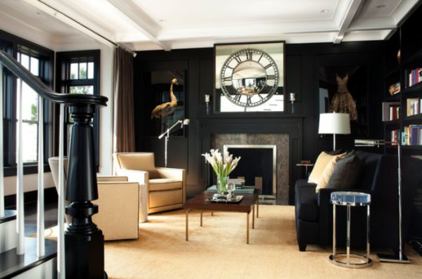 Living room with cream flooring, white ceiling and then black walls, with cream arm chairs and black sofa