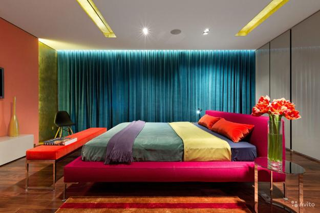 Modern bedroom with orange wall, teal curtains, pink bed and green bedding