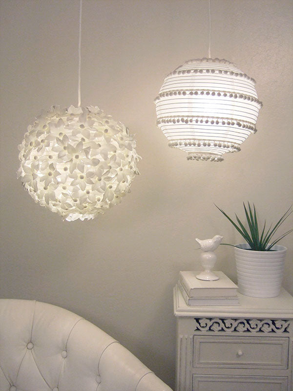White paper lanterns, one like flowers and the other bobbled