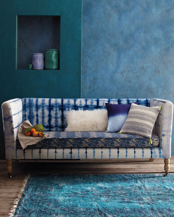 Dark blue living space with mottled walls, with tie dye style white and blue sofa