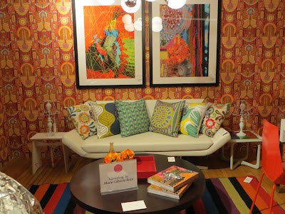 Seventies style orange and red wallpaper in an eclectically coloured warm living room
