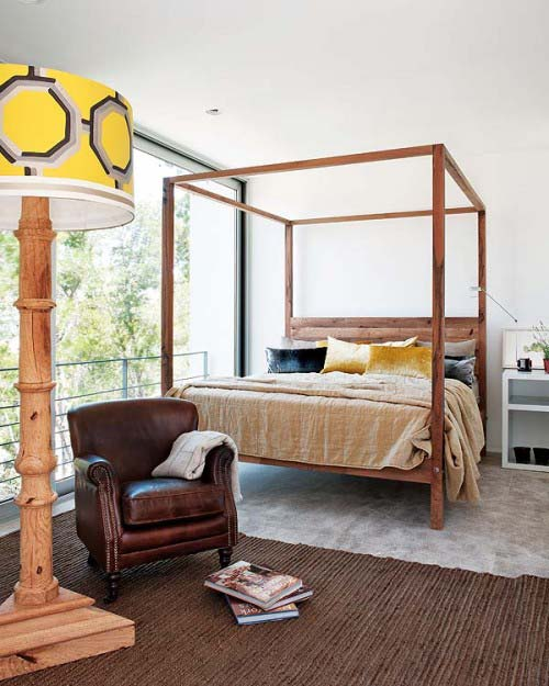 Four poster wooden cube bed, with large wooden floor lamp and yellow light shade