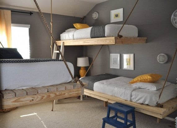 Grey and yellow bedroom with rope suspended beds, resembles cramped train sleeping carriages