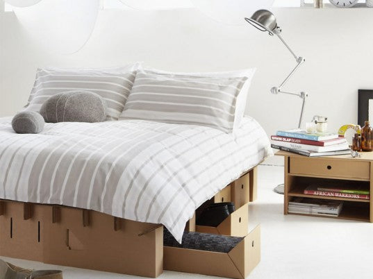Cardboard bed base and mattress with white and grey striped bedding