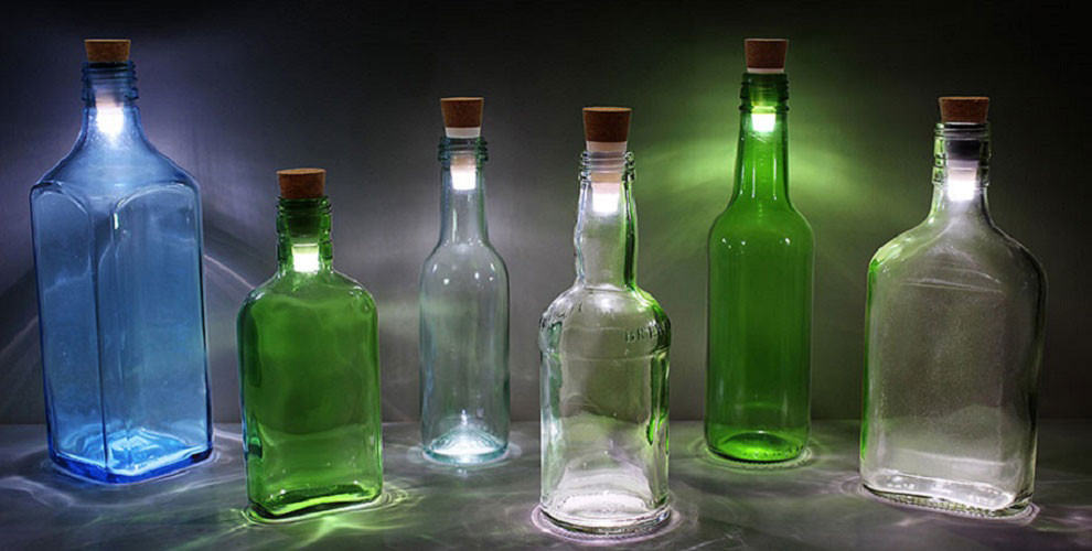 Different coloured bottles used as lamps, with rechargeable LED lights inside the lid