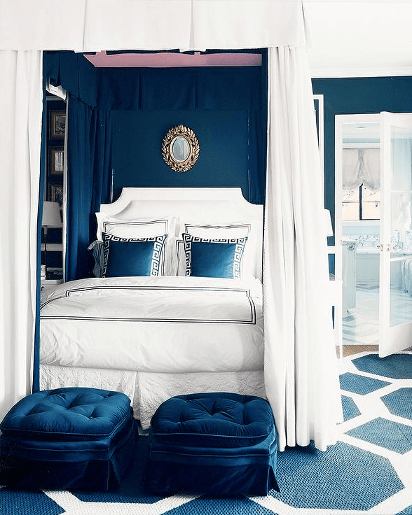 Luxurious four poster bed and canopy, with white bedding and blue accessories