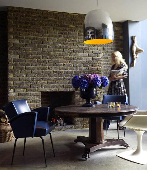 Lovely exposed natural brick wall and fireplace in a dining room with blue and cream chairs