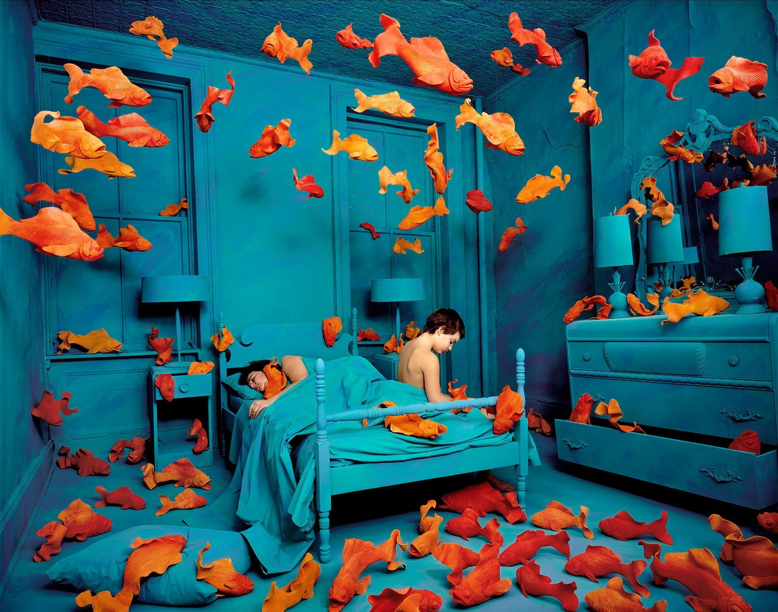 Underwater themed bedroom with all blue furniture and an array of gold fish suspended and on the floor