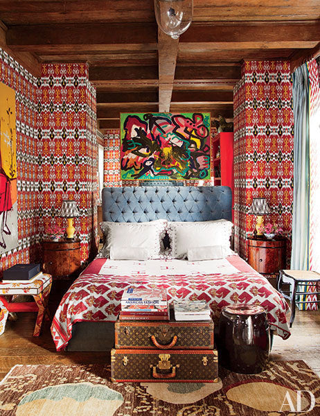 Funky red geometric wallpaper in a small yet stylish guest room