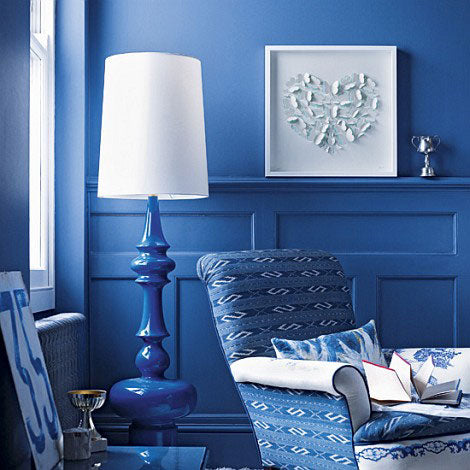 Deep blue living room, with blue chair, walls and lamp, then white accessories