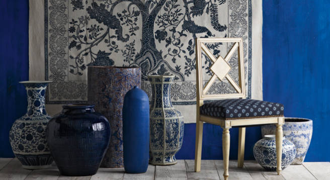 Blue and white accessories in front of a dark blue wall and wall tapestry