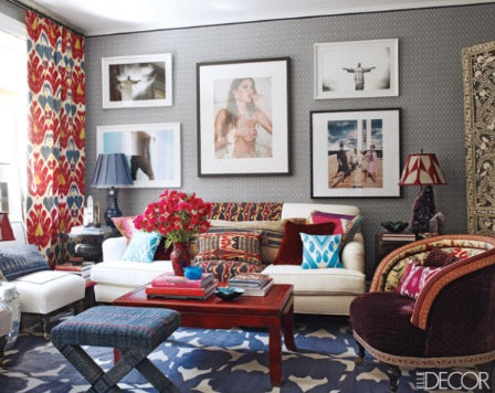 Grey living room with red curtains, a blue rug and white sofa covered in red patterned cushions