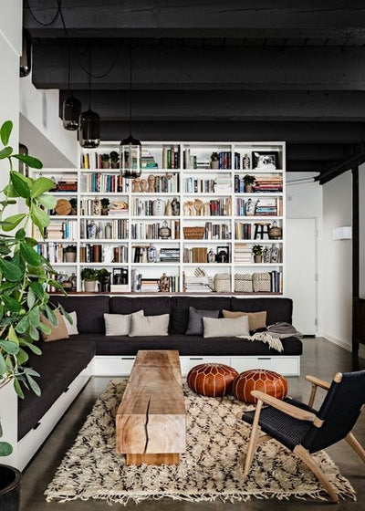 White sectional book shelves over one wall, with black corner sofa and solid tree trunk coffee table