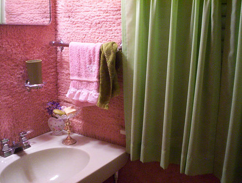 Pink bathroom with pink push walls and a green voile curtain panel over the window