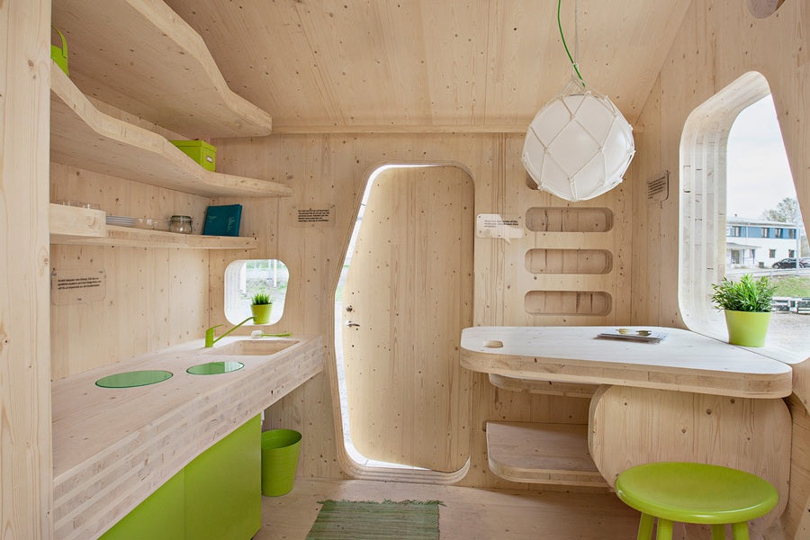 Small modular wooden home with natural wood finish and touches of lime green, such as green chairs, bins and plant pots