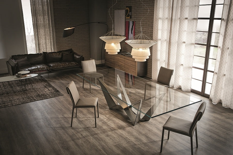 Industrial living room and dining room with glass table, brown leather sofa and exposed brick walls