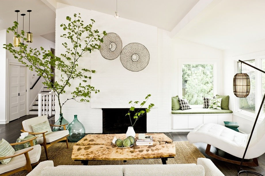Modern white living room with white sofa and chairs and touches of green and plant life