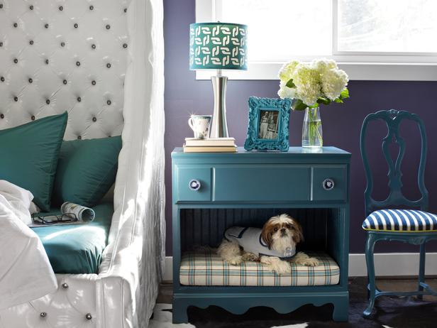 Purple bedroom with teal bedside table that doubles as a dog bed