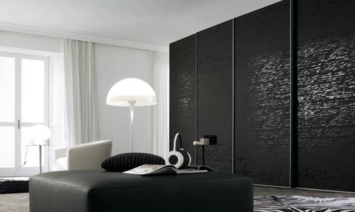 Black and white interior, with black sliding door wardrobes and white floor lamp