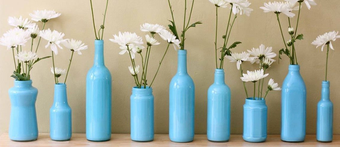 Light blue painted glass bottles containing white flowers