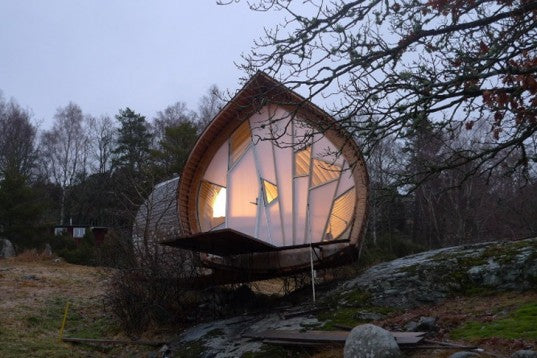 A self contained pod home with an upturned leaf shape showcasing unusual shaped glass panels, surrounded by trees