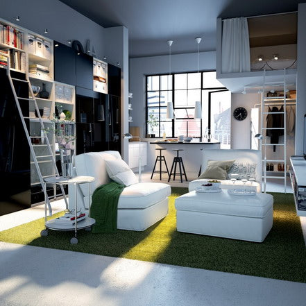 Modern living space with white single chairs and white ottoman on green grass like rug, black and white fitted wall units and sleeping space accessible via a ladder