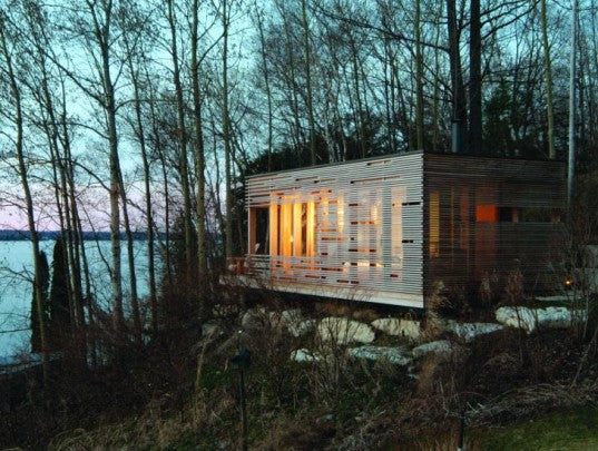 Wooden rectangular cube pod home, surrounded by trees and overlooking a lake