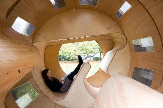 The interior of a small wooden modular home, with rotating sections for accessing different parts of the home