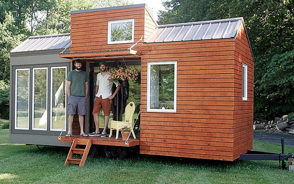 Small modular home half grey and half mahogany stained wood, that is on wheels like a caravan