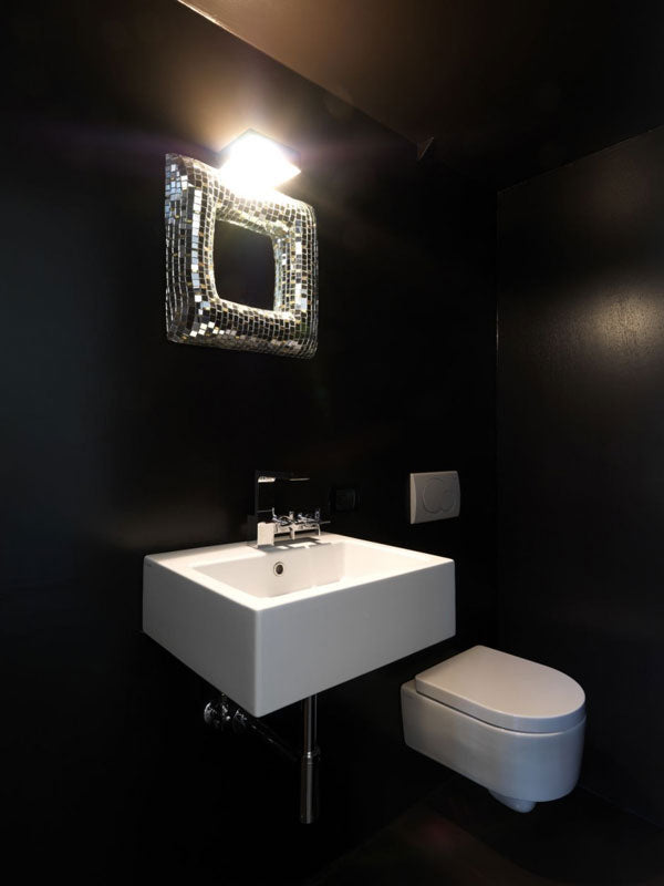 Black bathroom with white sink and toilet, plus small sparkly framed mirror