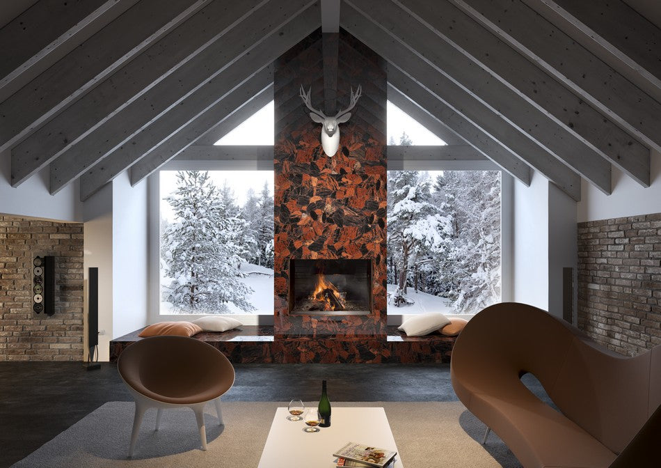 Living room with exposed white beam pitched roof and red ceramic column fireplace, with snowy trees seen through the windows