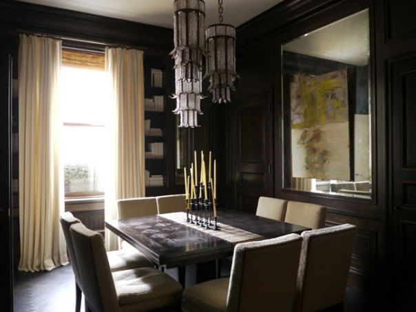 Luxury black dining room with large mirror, cream curtains and dining table with candles