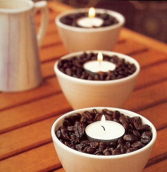 Lit candles in coffee cups, wedged in the centre of the cup by coffee beans filling the cup
