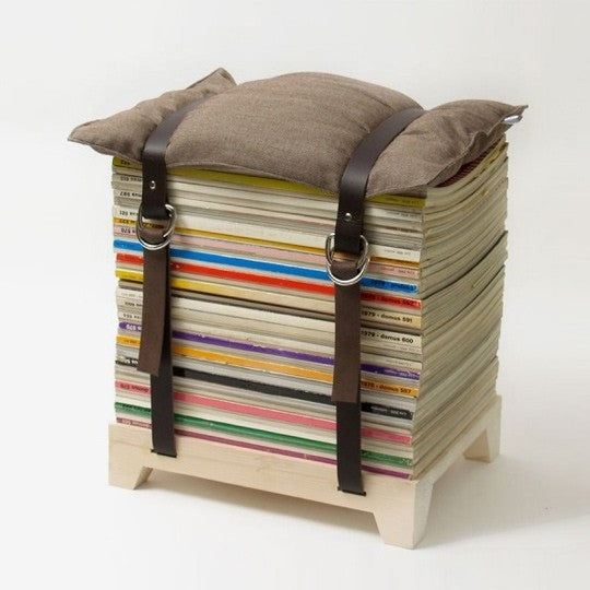 DIY stool made from a stack of books, with a brown cushion on the top attached with two brown belts