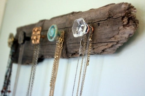 Wooden driftwood attached to a wall, with hooks on it for hanging jewellery